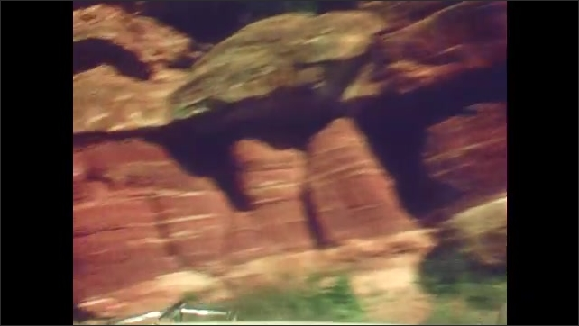 1940s: Car parked at large rock formations. Tourists walk around. Car drives through public park and rock formations.