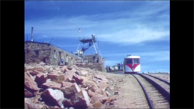1940s: Sightseeing train chugs up mountain, stops at station at top.