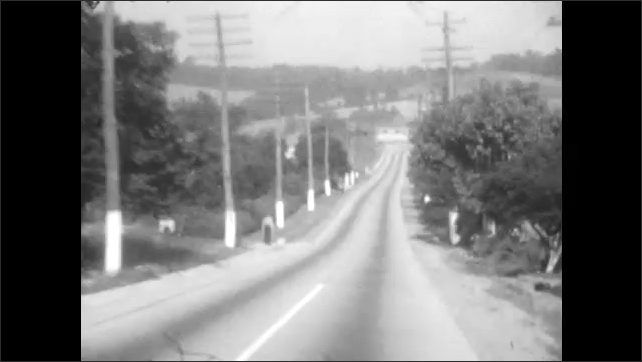 1920s: Car driving along two-lane road, with telephone poles and car passing in opposite direction. Vehicle goes under bridge and passes car that pulls out in front of it.