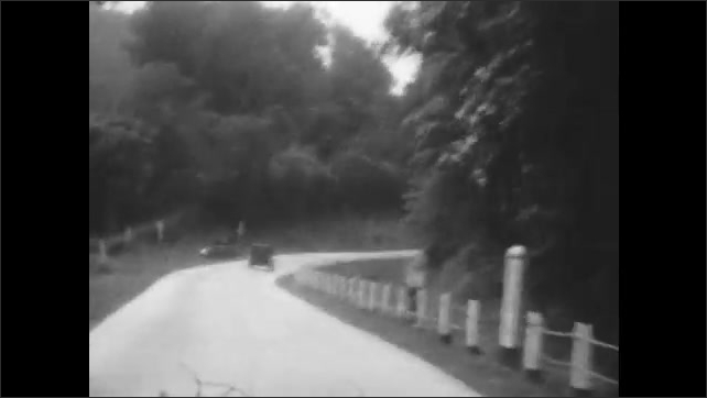 1920s: Vehicle driving along two-lane road in rural area with white fences on both sides of road.