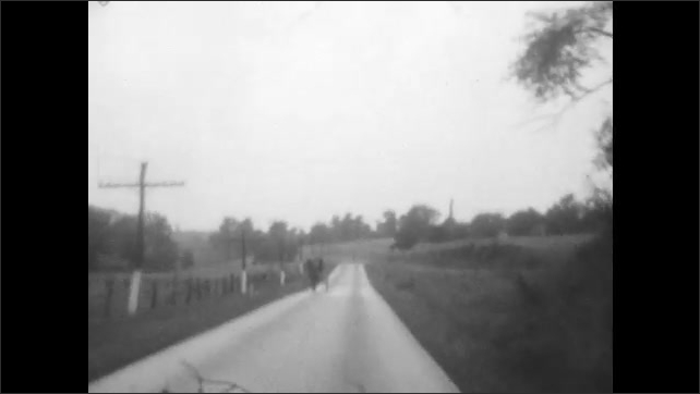 1920s: Vehicle driving in rural area, with white markers at edge of road. View from vehicle as horse and buggy pass in opposite direction. Vehicle navigates curve in road.