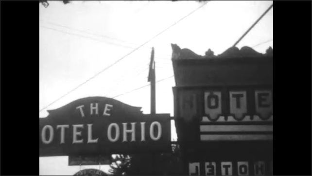 1920s: Car on road with several cars going in both directions. Vehicle goes up hill. The Hotel Ohio sign. Buick Champion Garage sign in front of buildings.