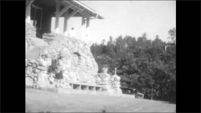 1920s:People outside building. Car drives on dirt roads