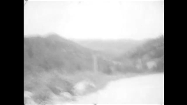 1920s:Car drives on dirt road in nature