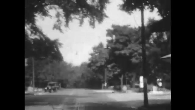 """1920s: View from car on street in residential area, with streetcar going by. Vehicle passes horse and buggy. Sign for Red """"G"""" Road Maps."""