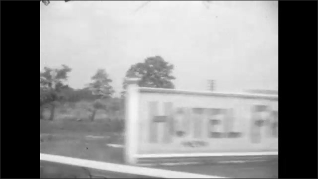 1920s: Car driving down road with power lines running parallel to it. Train passes by. Hotel Freeport billboard. Building with Hotel Freeport sign on the side. Woman and child walk through doorway.