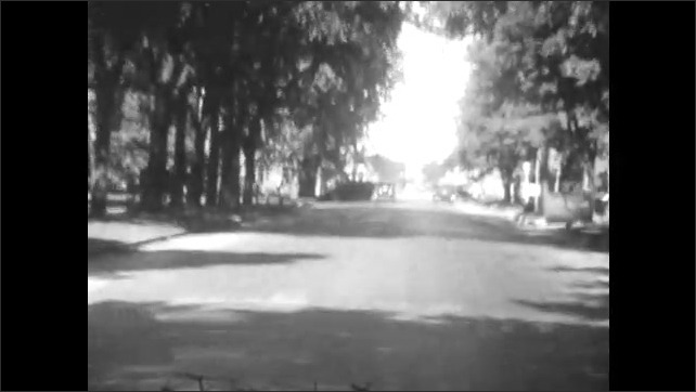 1920s: UNITED STATES: view of road and hill through vehicle window. Cars on road.