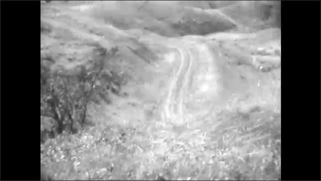 1920s: UNITED STATES: railings on mountain road. View of road from vehicle. View across hills and landscape.