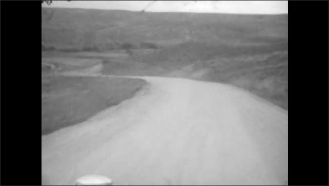 1920s: UNITED STATES: car drives down winding road on mountain. Car drives across bridge. View of track from car window