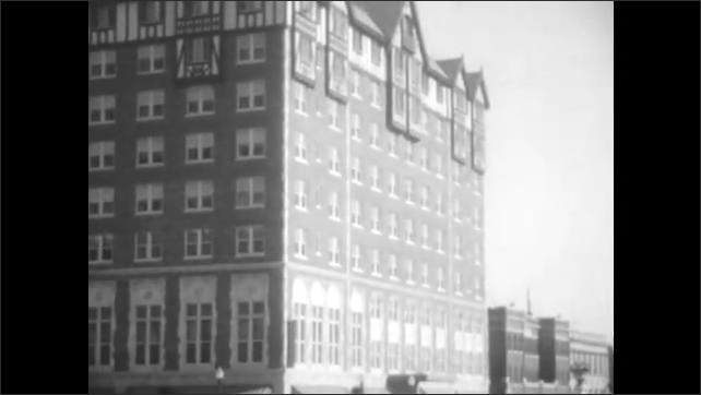 1920s: UNITED STATES: Alex Johnson sign. Plane in sky. Buildings by road. Man leaves building doors