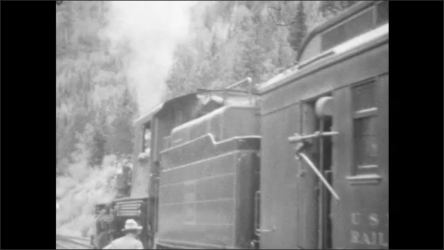 1920s: Train engine 331. Man sits in front seat of train engine. Train employee with hat and uniform stands on platform by train, smiles. Train chugs out of station.