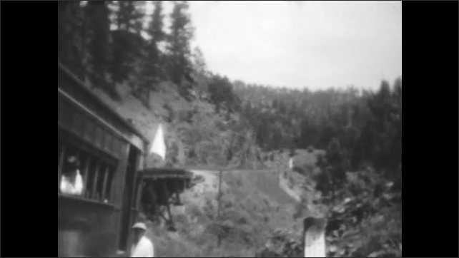 1920s: Man walks along train tracks. Man exits train. People wait on train. Train moves through mountains.