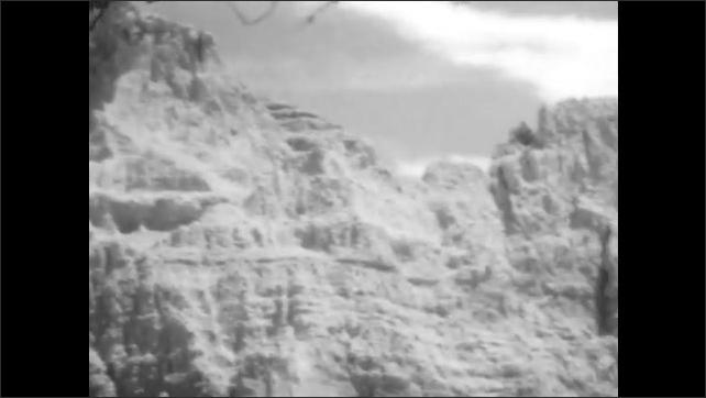 1920s: Mountains, trees, rocks, road through mountains.