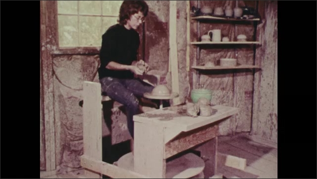 1970s: Woman sits at pottery wheel, molding clay. Hands hammering wood peg into furniture.