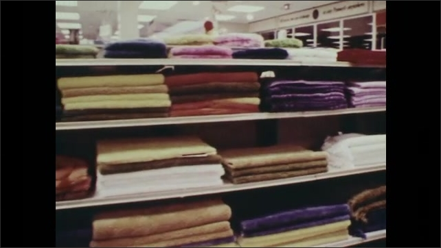 1970s: Towels are stacked on shelves in store for sale. Dinning and living room sets are on display for sale in store.