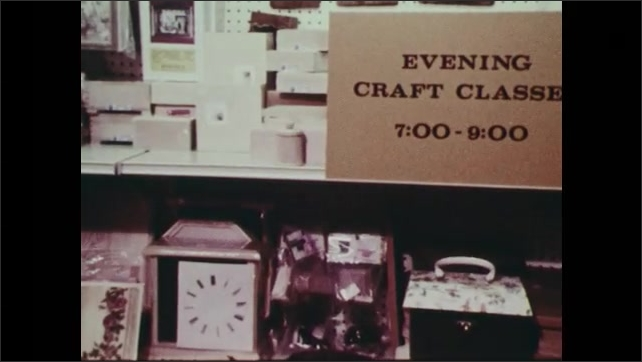 1970s: Assortment of products on shelves for sale in store. Sign for craft class. People walking outside of stadium.