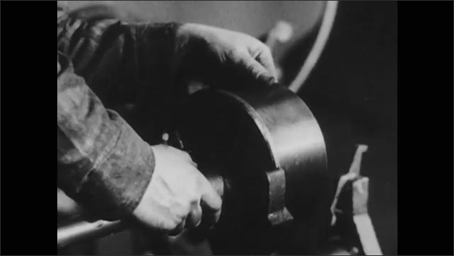 1940s: Close up of fist. Men working in factory. Shots of hands working with machine parts.
