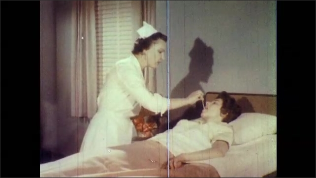 1960s: UNITED STATES: patient in bed. Sick lady in bed. Nurse takes patient's temperature. Close up of nurse's face. Nurse takes temperature