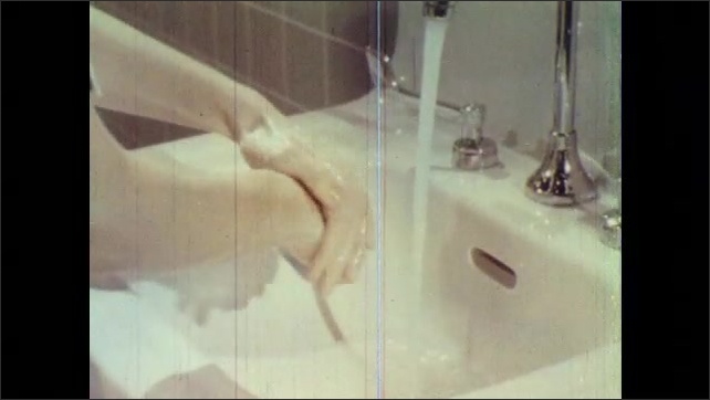 1960s: UNITED STATES: nurse washes hands in sink. Mechanical cleansing of hands. Soap lather on hands.