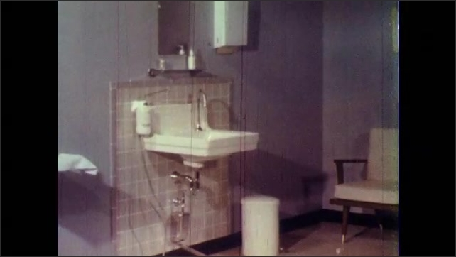 1960s: UNITED STATES: sink in hospital room. Liquid soap dispenser. Clean and contaminated objects in clinic. Hand lotion on wall.