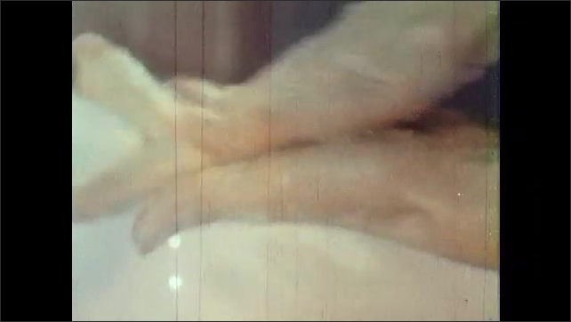 1960s: UNITED STATES: hands under water in sink. Nurse washes hands in sink. Soap on hands. Water runs from tap. Close up of interlaced fingers. Friction motions on hands.