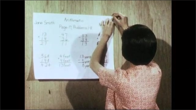 1960s: poster with cursive essay covers hangs on wood paneling. Woman push pins arithmetic problems on sheet of paper to wall in school classroom.
