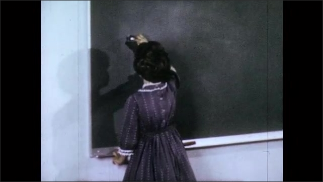 1960s: woman bends over to assist boys and girls at desks as boy and girl write words on blackboard with chalk. feet sneakers stand near wall.