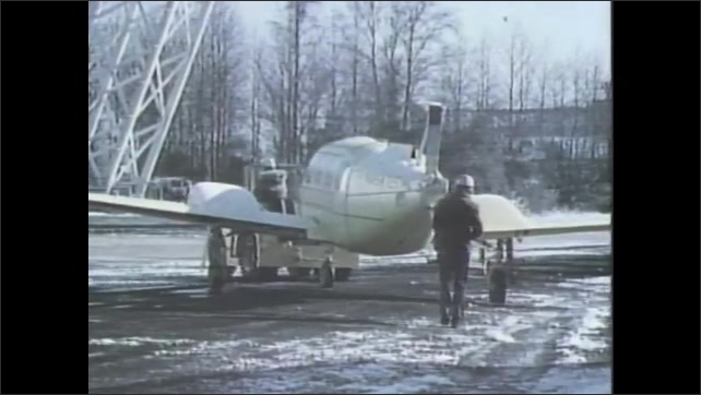 1970s: Light aircraft lands on landing strip. Vehicle pulls aircraft. NASA Langley Research Center. Man walks behind aircraft that is towed. A big crane moves space aircraft, trees in background.