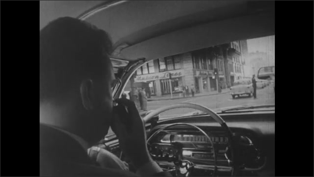 1950s: A man driving a car through a city picks up a CB radio and speaks into it.