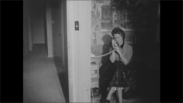 1950s: A man picks up a phone and dials. Other people dial. The internal mechanism of a phone and switchboard. A woman sits, speaking on a phone while her son walks by. A man and woman hang up.