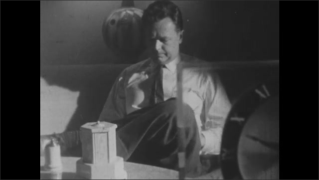 1950s: A tabletop cigarette holder closes. A man sitting on a couch lights a cigarette with a match. A clock shows the time as 9:30.