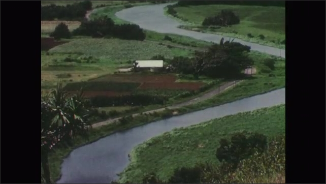 1950s: Mountain vista near ocean. Clouds hang over fields of grass. Mountain looms over valley. River twists through farmland. Hand drops sugar cube into coffee. Pineapples ride along conveyor belt.