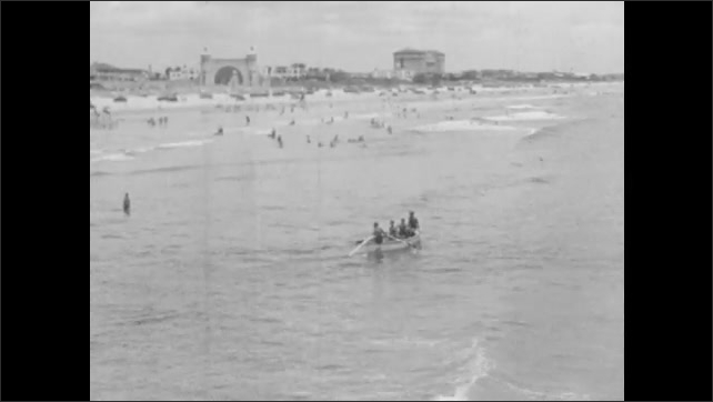 1940s: Lifeguards sit in a chair at the beach. Swimmers and rowers in the water. Buildings on the shore.