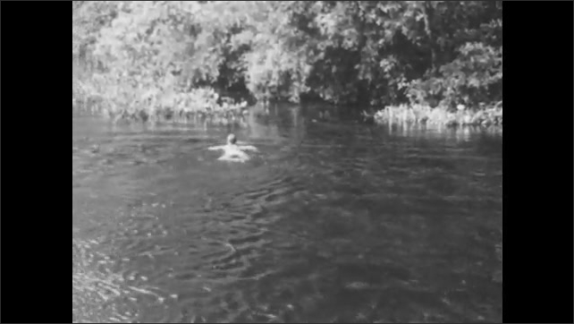 1940s: A swimmer swims along with the current toward the shore, where he stands up.