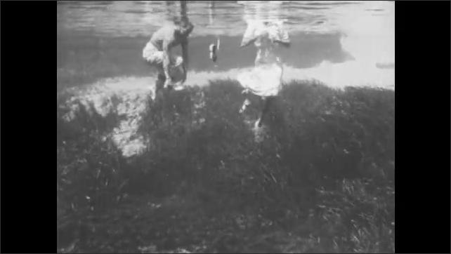 1940s: A man and woman tread water. They duck under water and remove their shoes and clothing.