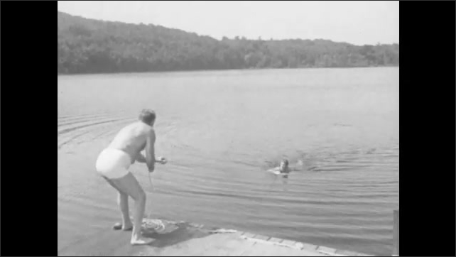1940s: A man pulls a distressed swimmer in to shore using a ring buoy lifesaver.