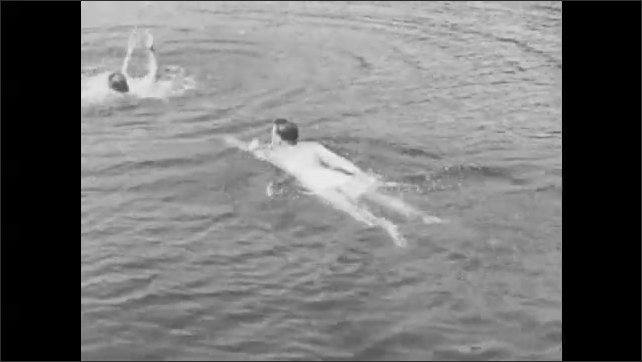 1940s: A man swims toward a distressed swimmer. He grabs him by the hair and pulls him to safety.