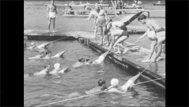 1940s: Members of a lifesaving class dive into the water with buoys while others hold ropes from the shore. They pull swimmers to safety. Swimmers dive in with kick boards and swim out.