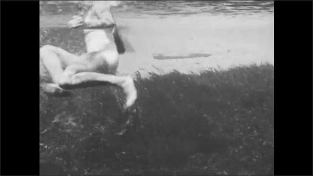 1940s: A woman swims through the water. She stops and reverses direction. View from above and below the water.