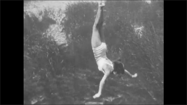 1940s: A woman swims across the surface of the water. She turns and dives below. View from above the water and below.