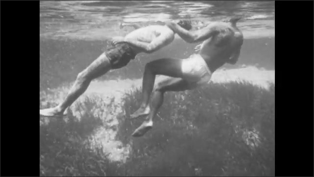 1940s: A swimmer lifts a distressed man to the surface of the water. He grabs him by the chin from behind and pulls him through the water.