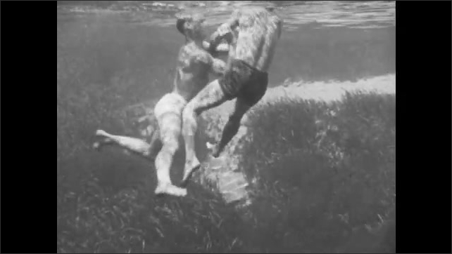 1940s: A man approaches a distressed swimmer in the water. As the troubled swimmer tries the grab hold of his arm, the man blocks him and turns him around. He pulls him by his chin from behind.