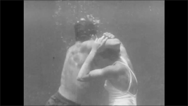 1940s: A woman approaches a struggling swimmer in the water. He grabs her by the head. She breaks free and gets her head above water, then pull him up and tows him along the surface by his chin.