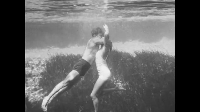 1940s: In slow motion, woman approaches a struggling swimmer in the water. He grabs her by the head. She breaks free and pulls him toward the surface.