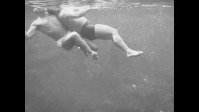 1940s: A man approaches a struggling swimmer  in the water. He tows him backward with his arm wrapped around his chest, keeping the man's head above water.