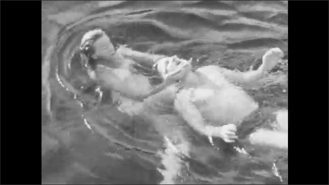1940s: A woman approaches a struggling swimmer in the water. She pull him to the surface by his arm and tows him backward with her hands on either side of his face.