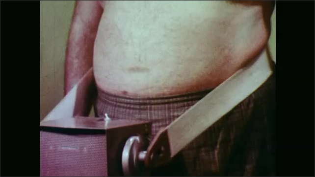 1970s: Man stands with no shirt on in front of machine with belt strapped around waist to machine, as belt moves. Woman in front of mirror puts white cream on face.
