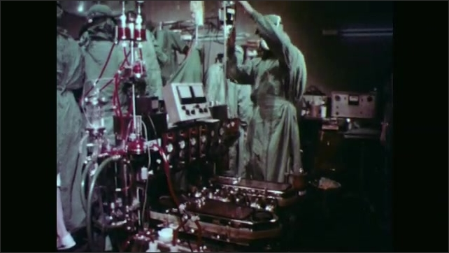 1970s: Doctors monitor machinery in operating room.