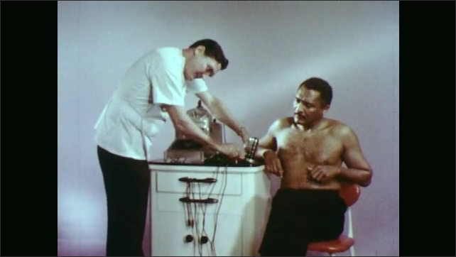 1970s: Shirtless man sits in chair. Doctor talks to man. Doctor plugs in machine parts, places man's hands on machine.