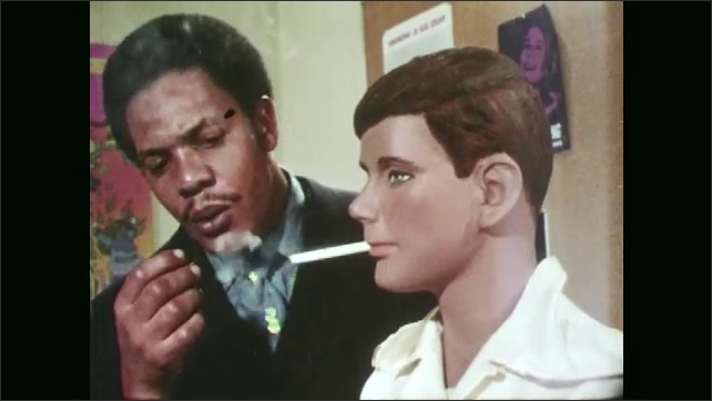 1970s: Mannequin with cigarette in mouth. Man lights cigarette in mannequin's mouth, mannequin smokes cigarette.
